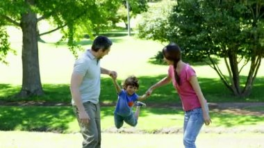 Parents swinging their son between them — Stok video