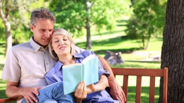 Affectionate couple sitting on park bench reading — Stock Video