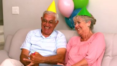 Senior couple celebrating a birthday on the couch — Stockvideo