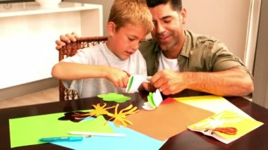 Father and son making paper shapes together at the table — Stok video