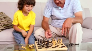 Senior man sitting on couch with his grandson playing chess — Stock Video