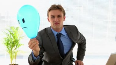 Grumpy businessman holding sad face balloon over face — Stock Video