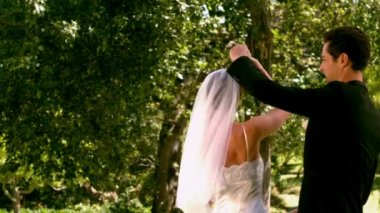 Happy newlywed couple dancing in the park — Stockvideo