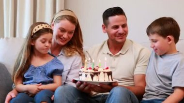 Young family sitting on sofa celebrating a birthday — Stock Video