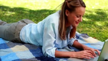 Blonde using her laptop lying on a blanket in the park — Stock Video
