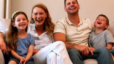 Young family laughing on couch — Stock Video