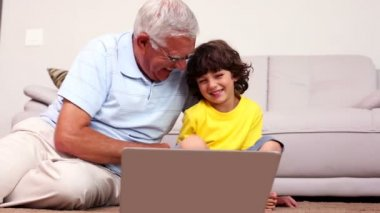 Senior man sitting on floor with his grandson using laptop — Stock Video