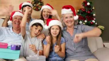 Happy extended family waving at camera at christmas time — Stock video