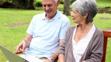 Gepensioneerde paar zittend op een bankje met behulp van een laptop — Stockvideo