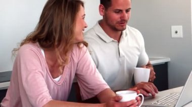 Couple having coffee and using laptop in kitchen — Stock Video