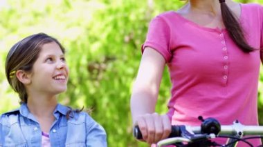 Mother and daughter on a bike ride in the park together — Stock Video