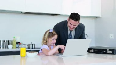 Father using the laptop with his daughter before work — Stock Video