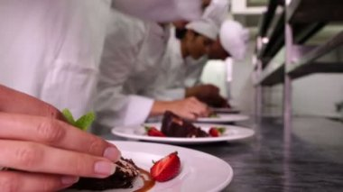 Chefs garnishing dessert plates with mint leaves — Stock Video
