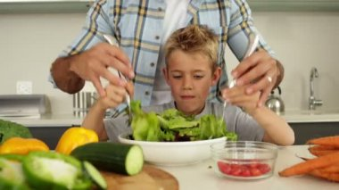 Father showing his cute son how to toss a salad — Stockvideo