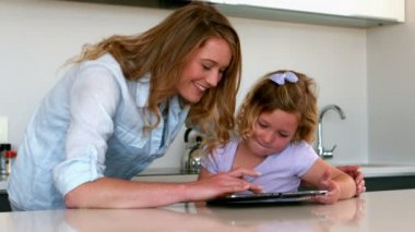 Mother using tablet with her daughter in the kitchen — Vídeo Stock