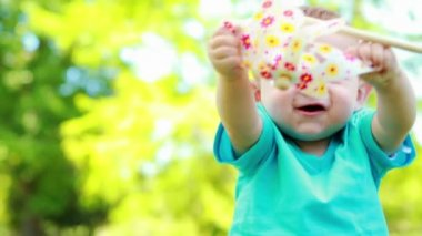 Cute baby boy playing with a pinwheel — Stock Video