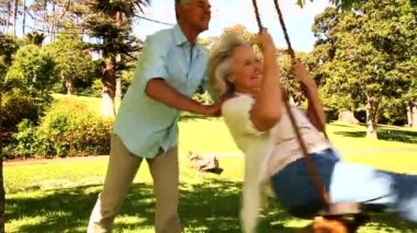 Retired man pushing his wife on swing — Stock Video