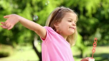 Little girl playing with bubbles in the park — Stock Video