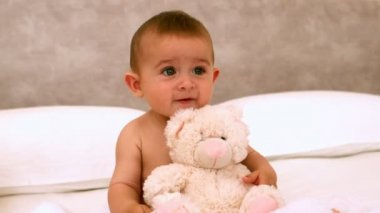 Cute baby on a bed with teddy bear — Stock Video