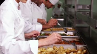 Chefs preparing food in serving trays — Stock Video