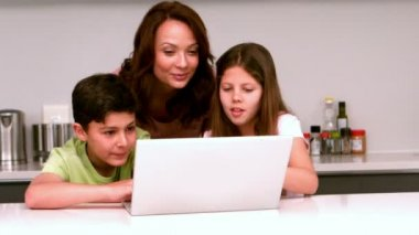 Mother using laptop with her children in kitchen — Stock Video