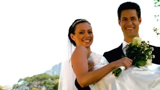 Couple de jeunes mariés heureux dans le parc — Vidéo