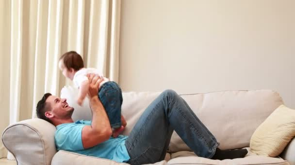Père jouant avec son petit garçon sur le canapé — Vidéo