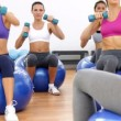 Fitness class sitting on exercise balls lifting hand weights — Stock Video
