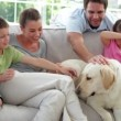 Family relaxing together on the couch with their dog — Stock Video #42651279