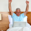 Senior man sitting in bed using laptop and cheering — Stock Video #42651641