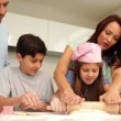 Mother helping daughter to roll out dough with her family — Stock Video #42651921