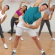 Aerobics class stretching together led by instructor — Stockvideo