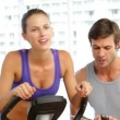 Trainer timing his client on exercise bike — Stock Video #42653003