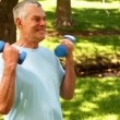 Retired man lifting weights outside — Vidéo