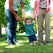 Parents teaching their baby son to walk on the grass — Stock Video