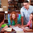 Students studying together in the library with their tutor — Vídeo de stock