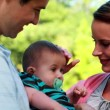 Proud parents holding baby son in the park — Stockvideo