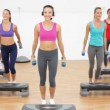 Aerobics class stepping together led by instructor — Stockvideo
