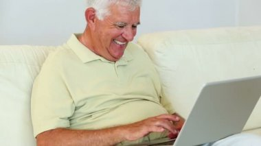 Senior man sitting on sofa using laptop — Stock Video