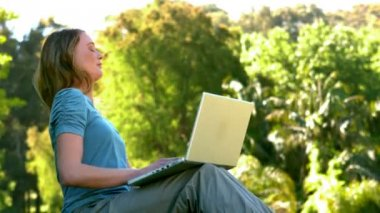 Young woman using laptop in the park — Stock Video