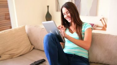 Pretty brunette relaxing on the sofa using her tablet pc — Stock Video