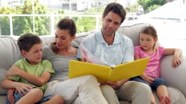 Family relaxing together on the couch looking at photo album — Stockvideo