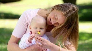 Glad mamma håller hennes flicka i parken — Stockvideo