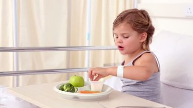Little girl lying in hospital bed eating her lunch — Stock Video