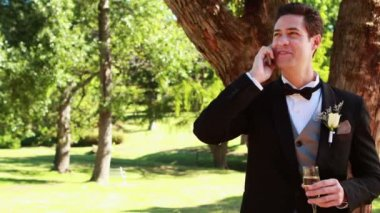 Happy groom drinking champagne and chatting on phone — Vidéo