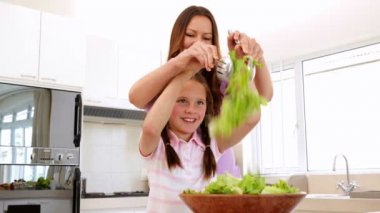 Mother showing her daughter how to toss a salad — Stock Video