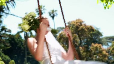 Pretty bride sitting on a swing — Stockvideo