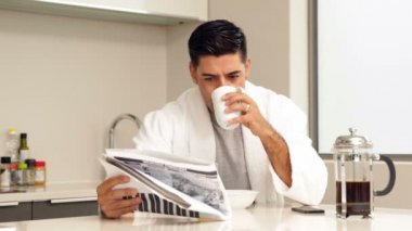Handsome man drinking coffee and reading newspaper — Stock Video