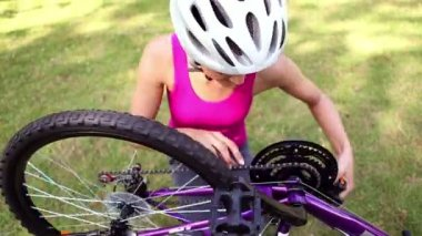Fit girl fixing the chain on her bike — Stock Video