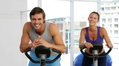 Fit couple exercising on bikes in fitness studio — Stock Video